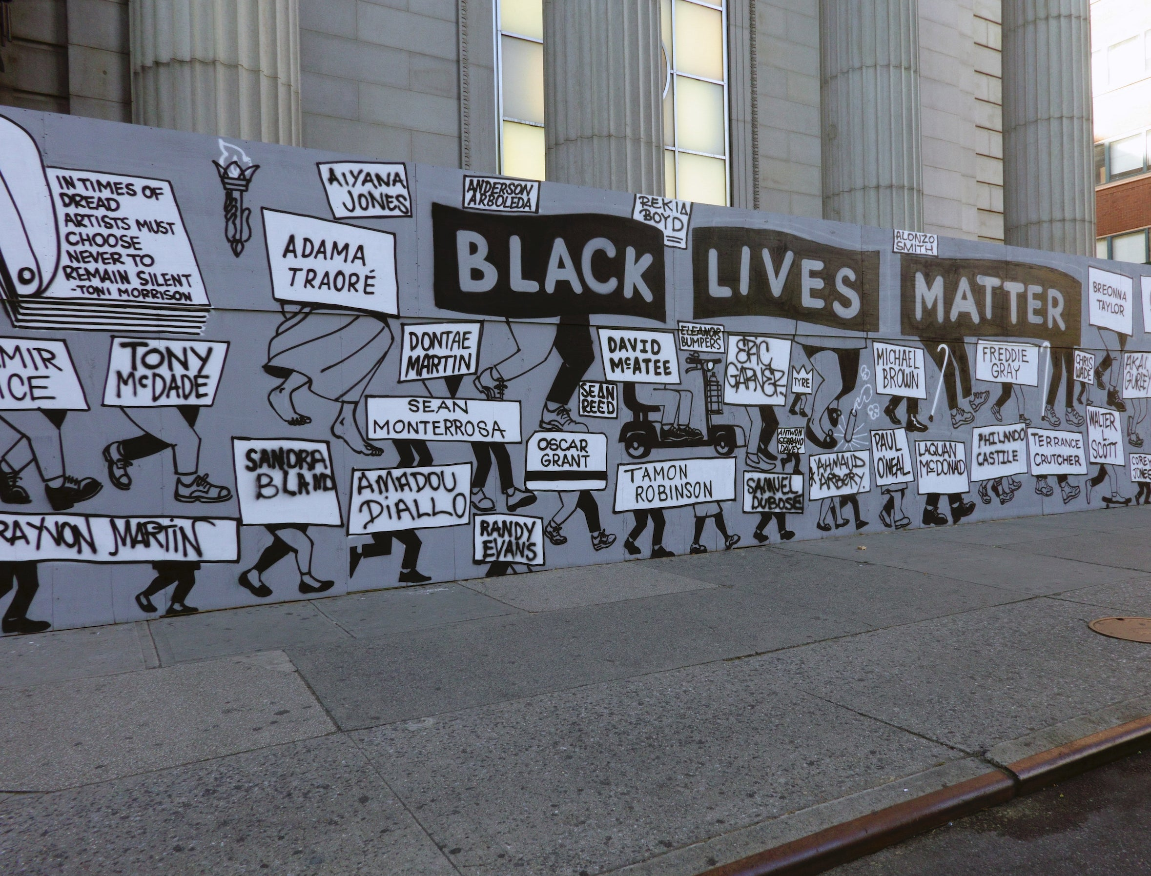 """A wall painted to say """"Black Lives Matter,"""" with painted signs that read the names of victims of police brutality and killings"""