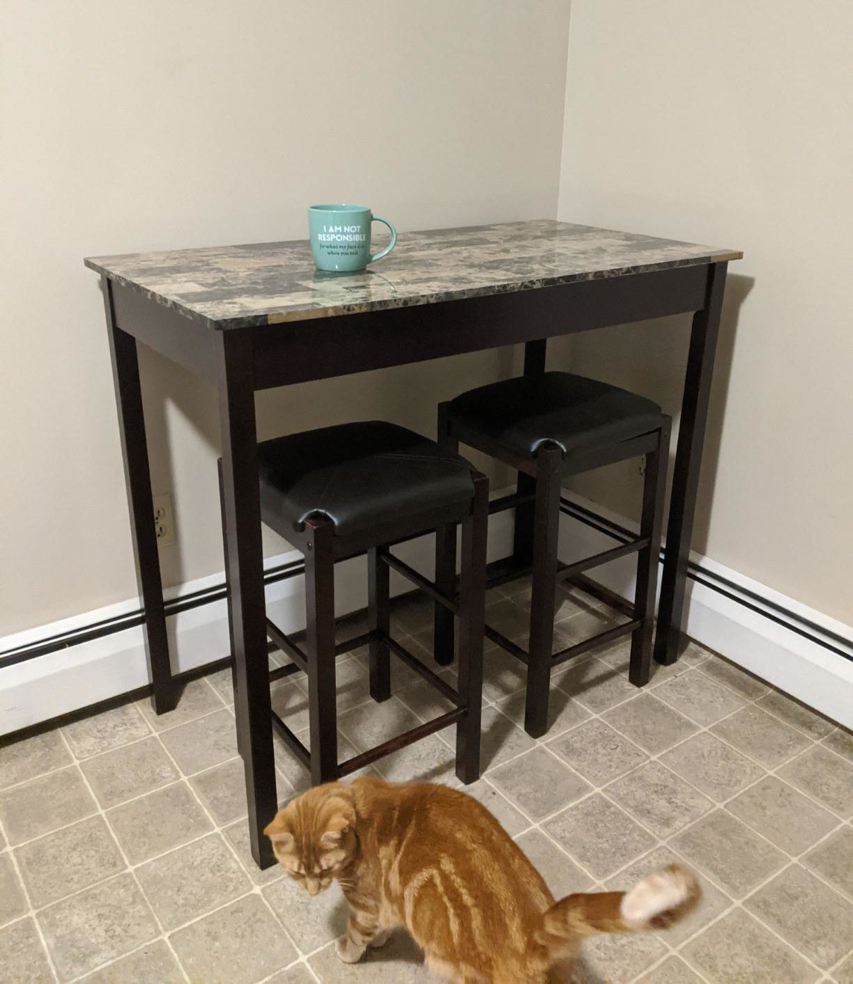 Reviewer pic of the tall table in brown with a marble-like top and two stools under it, also in brown