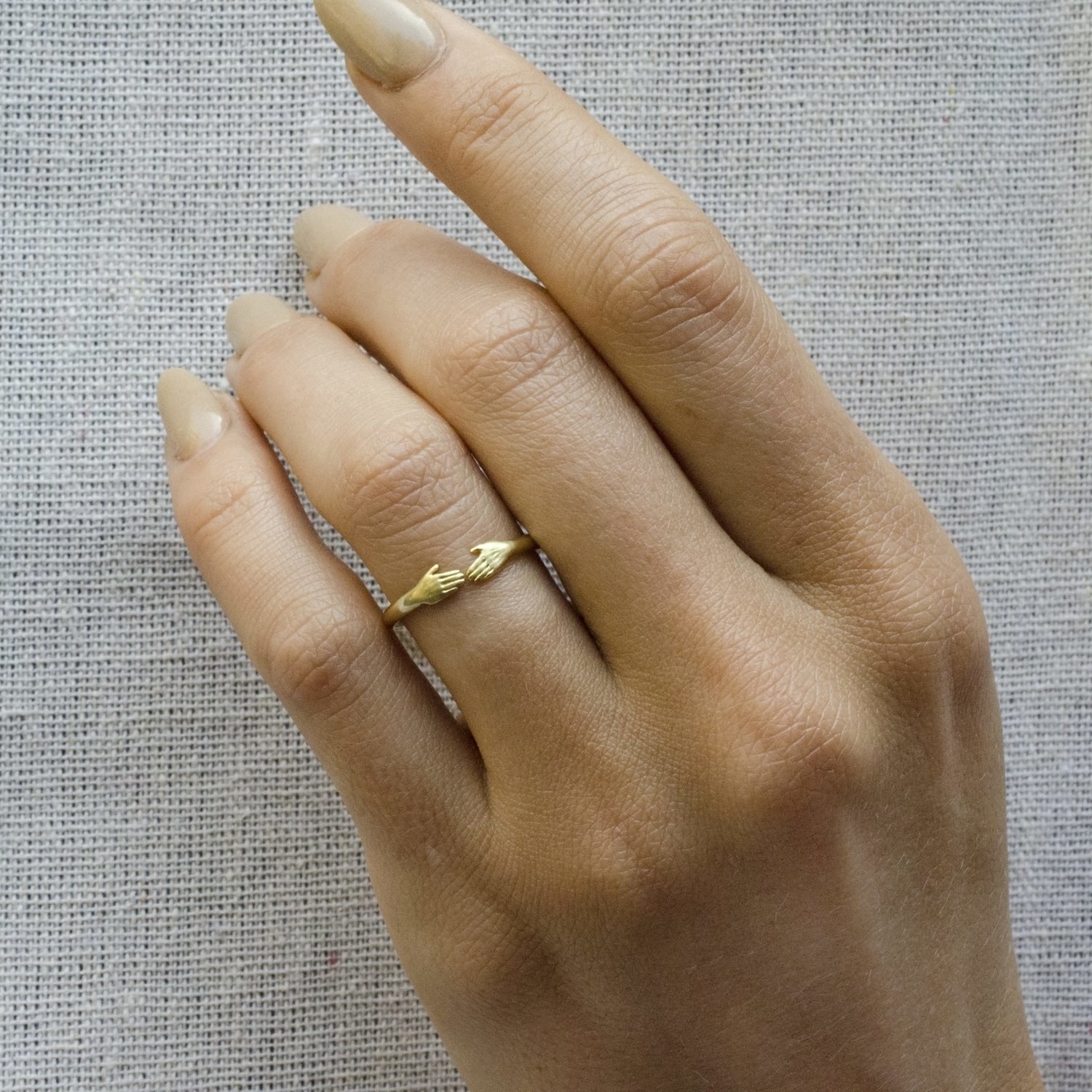 model wearing gold ring with two hands connecting