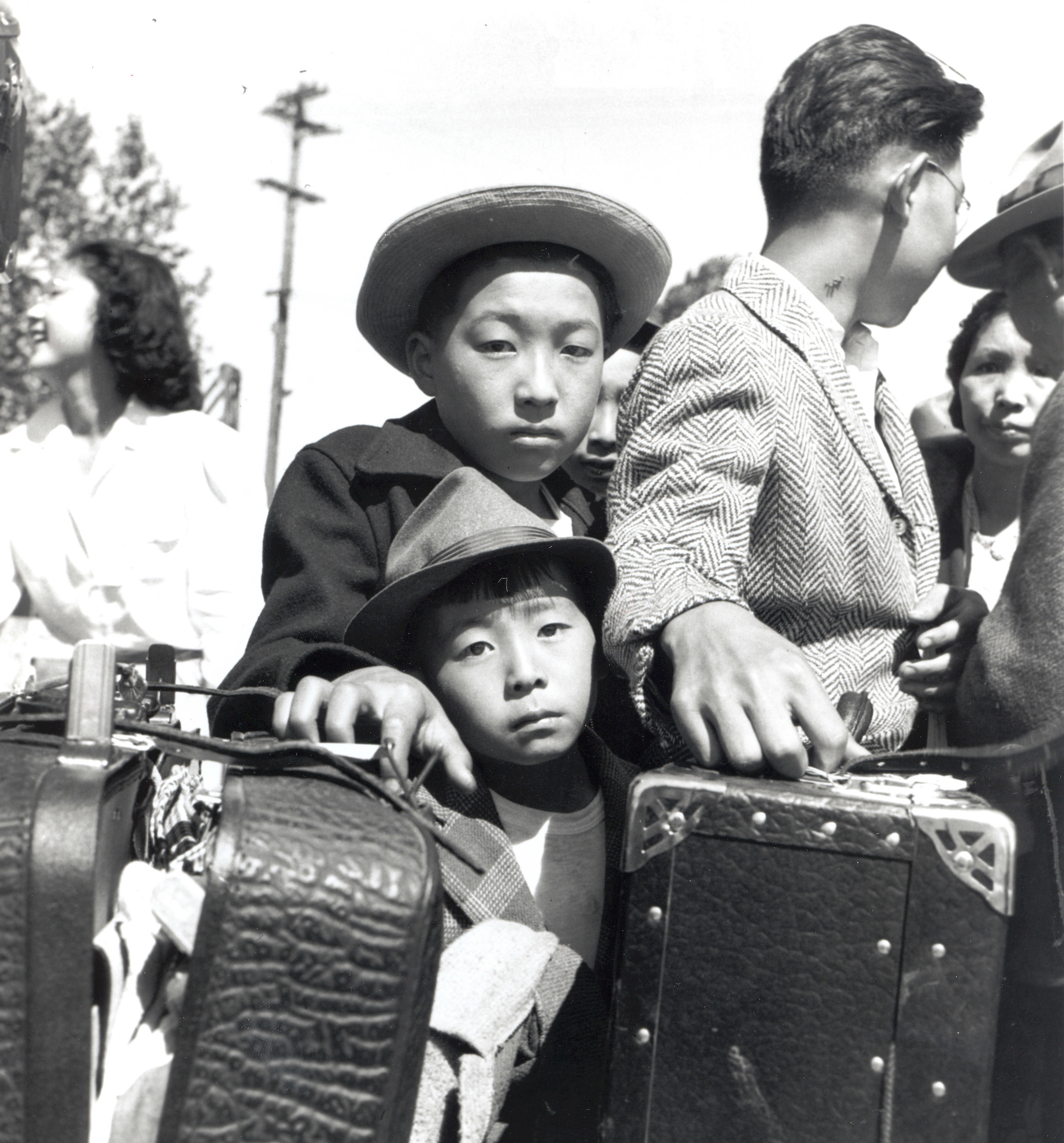 Two young Japanese boys with their family and suitcases are waiting for baggage inspections at an internment camp