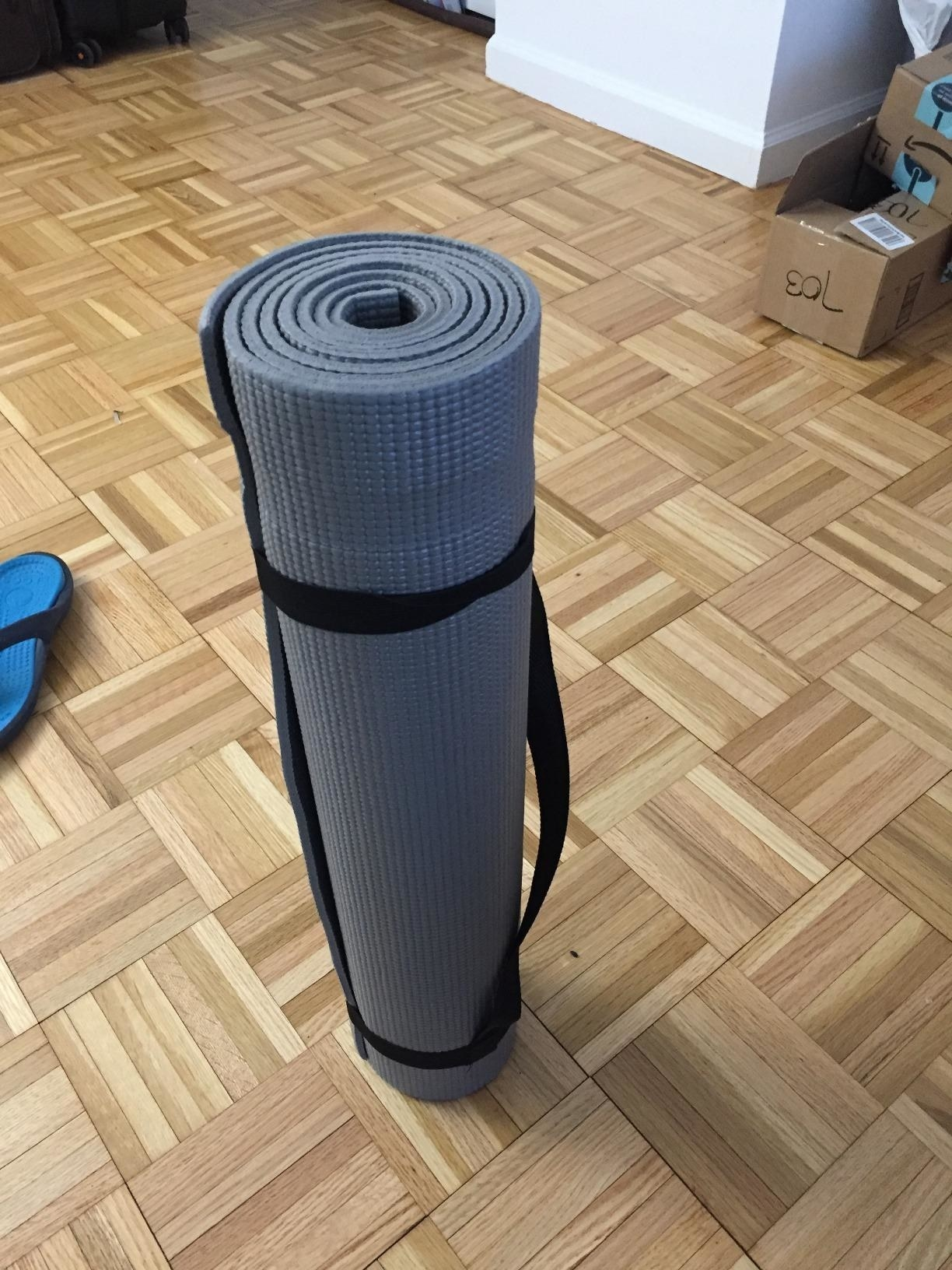 A reviewer showing the yoga mat rolled up and being held in place with the included straps