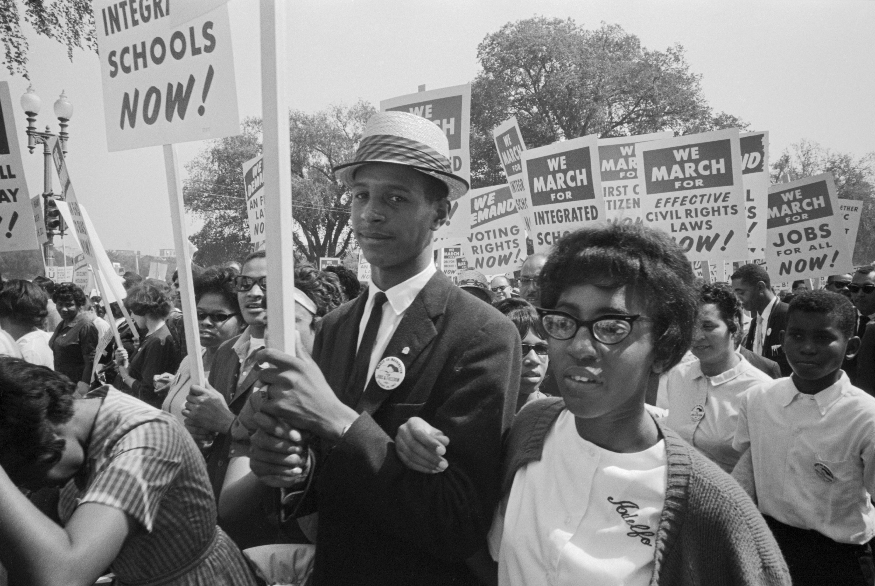 A young Black girl and boy marching with Black students, holding signs that call for integrated schools, voting rights, jobs, and civil rights