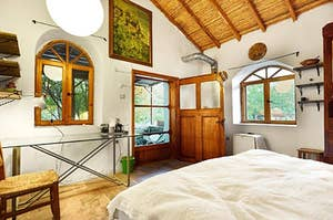 light-filled cottage bedroom with arched windows and wooden accents
