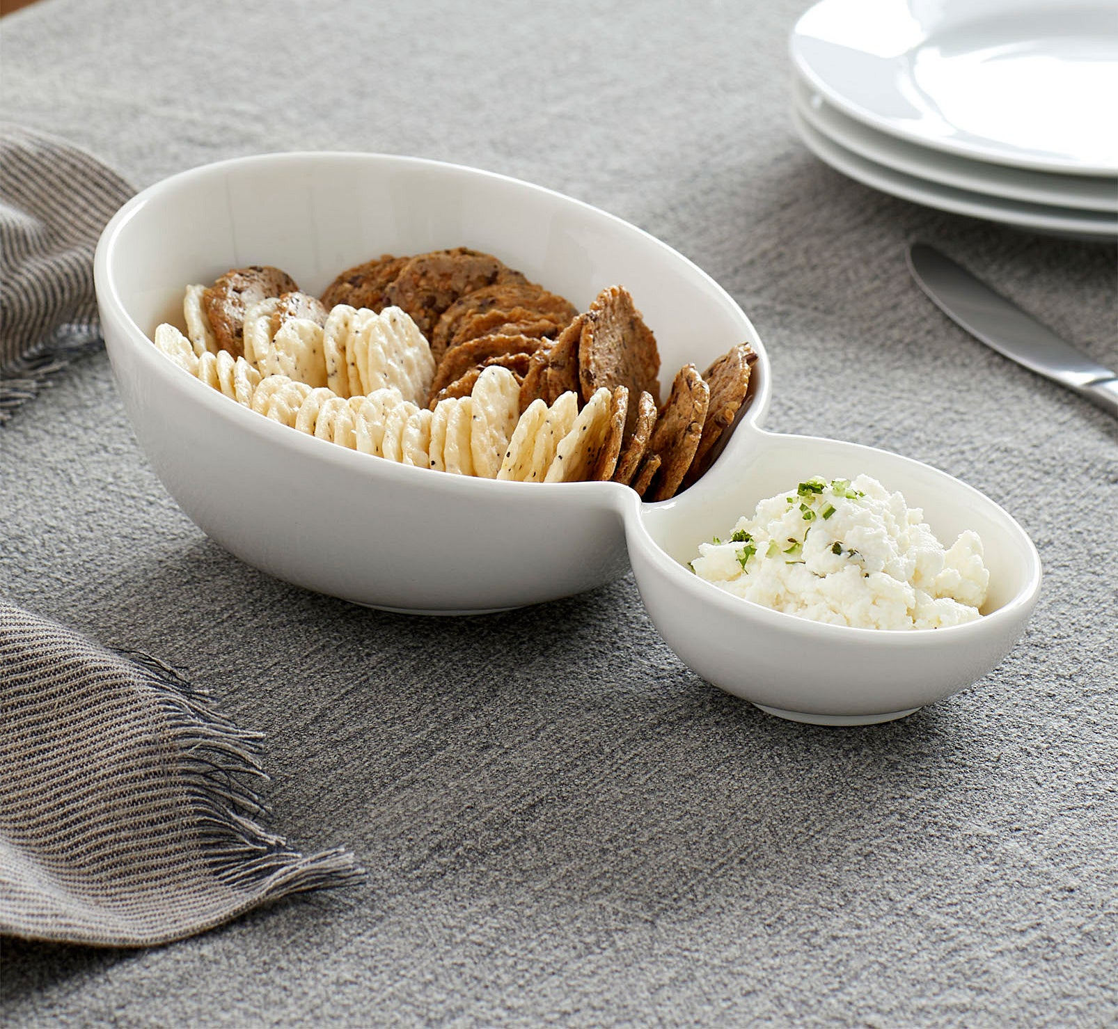 A ceramic bowl split into a large section with chips and a small section with dip