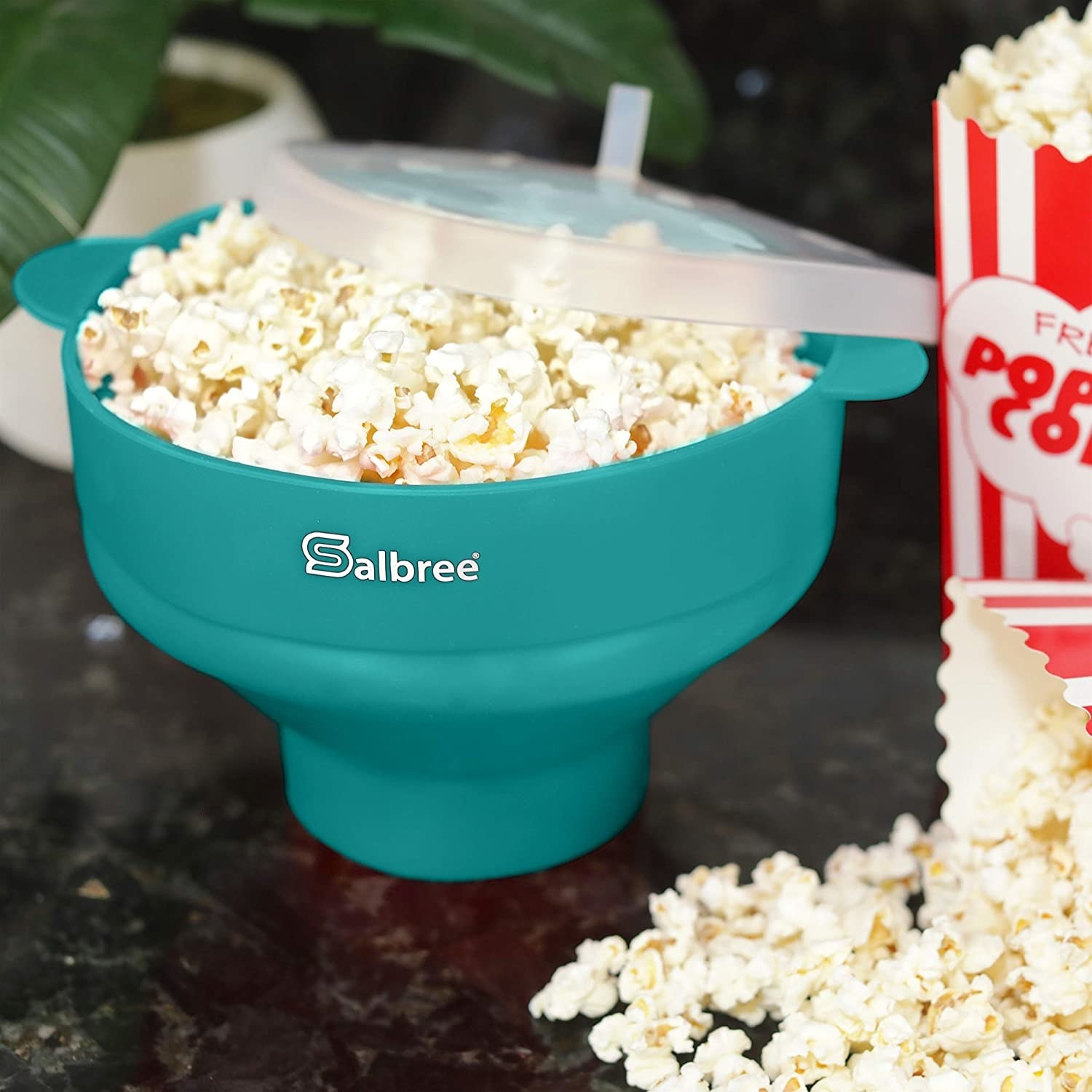 The popping bowl in the aqua color holding popcorn that was just made inside of it