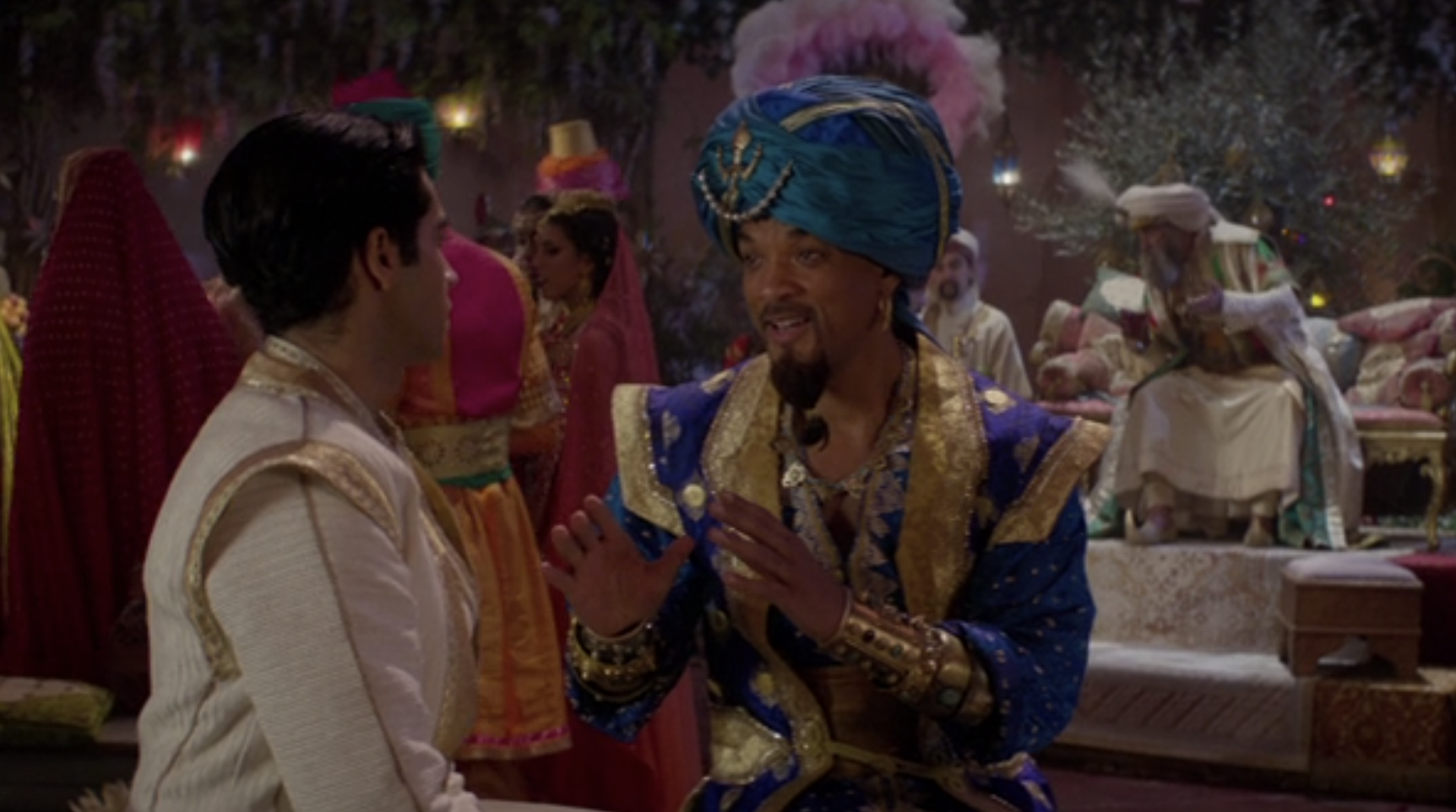 """Mena Massoud as Aladdin and Will Smith as Genie talking to each other during a party in the live-action """"Aladdin"""""""