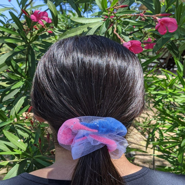 a model wearing the worm scrunchie in pink and blue