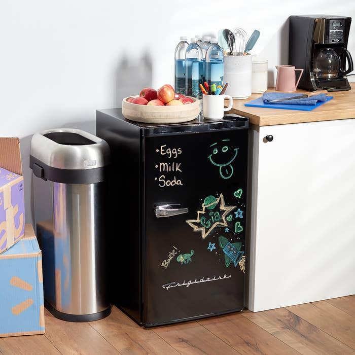 black mini fridge with dry erase writing on the front
