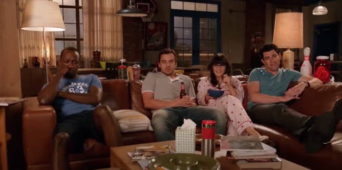 """The roommates on """"New Girl"""" sit on the couch together and watch TV."""