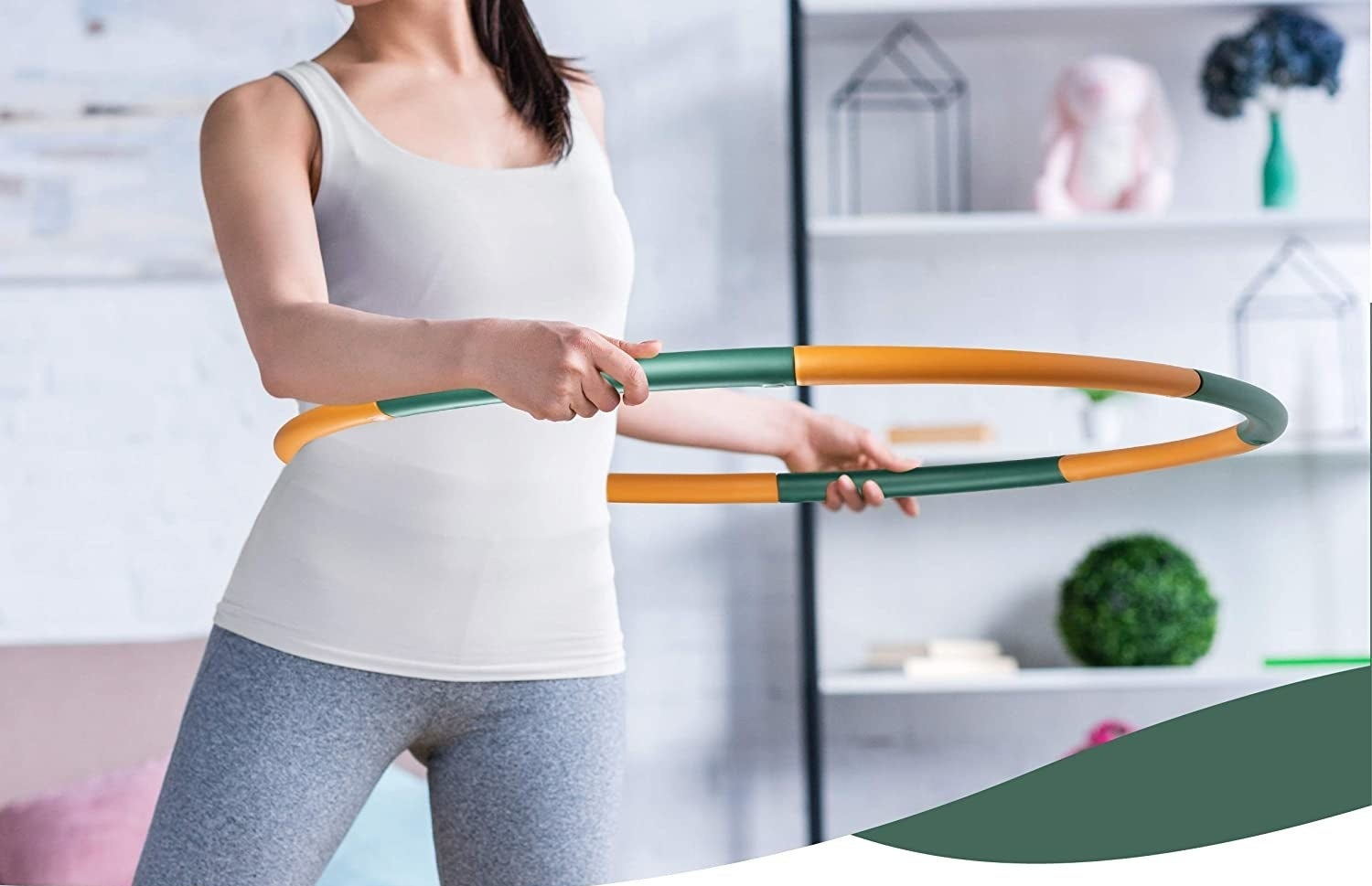 A model with the green and orange hula hoop around their waist