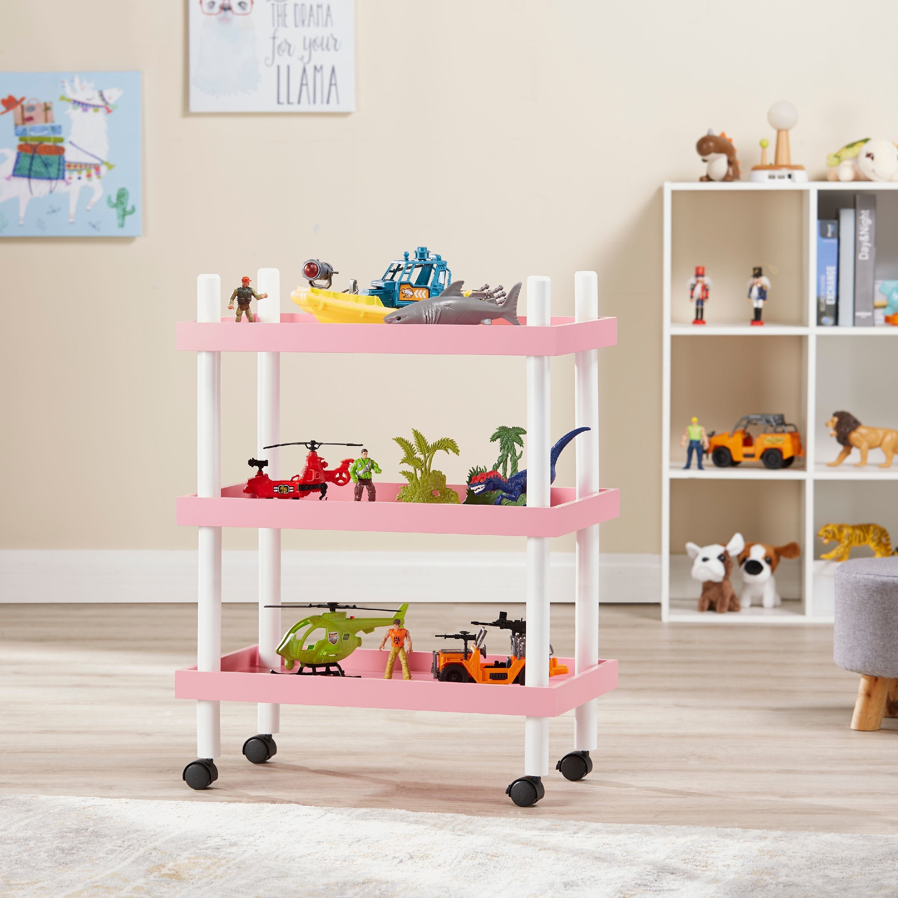 three tier pink and white rolling cart with toys on it