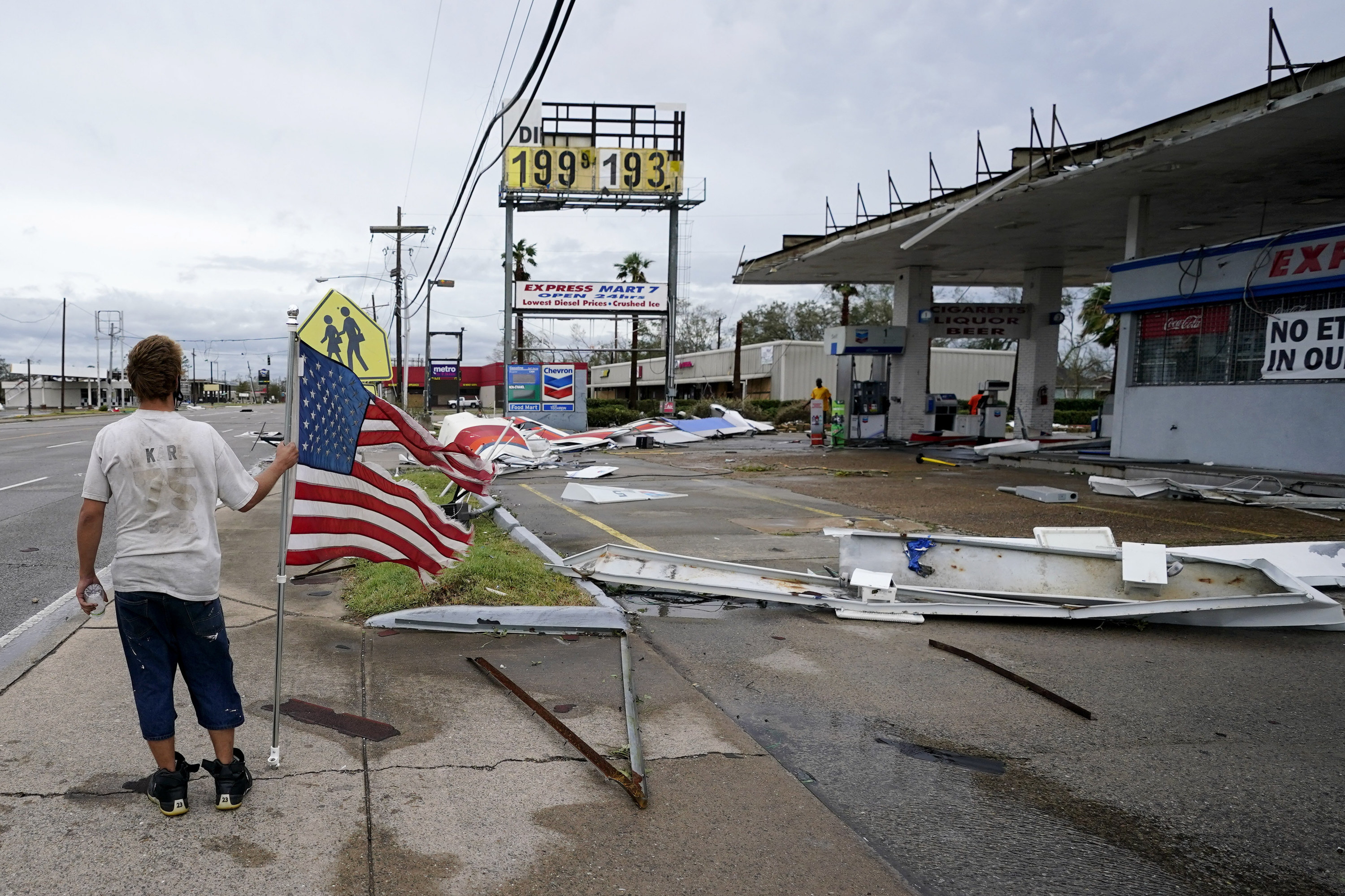 a man stands with a flag next to a lot of debris