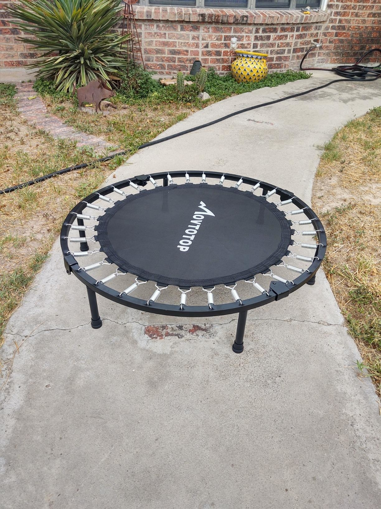A reviewer showing the mini trampoline with six legs