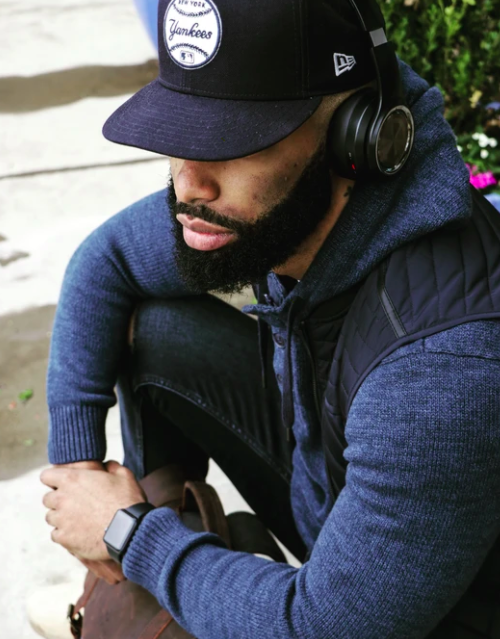 Model sits on sidewalk wearing a baseball cap and black wireless headphones