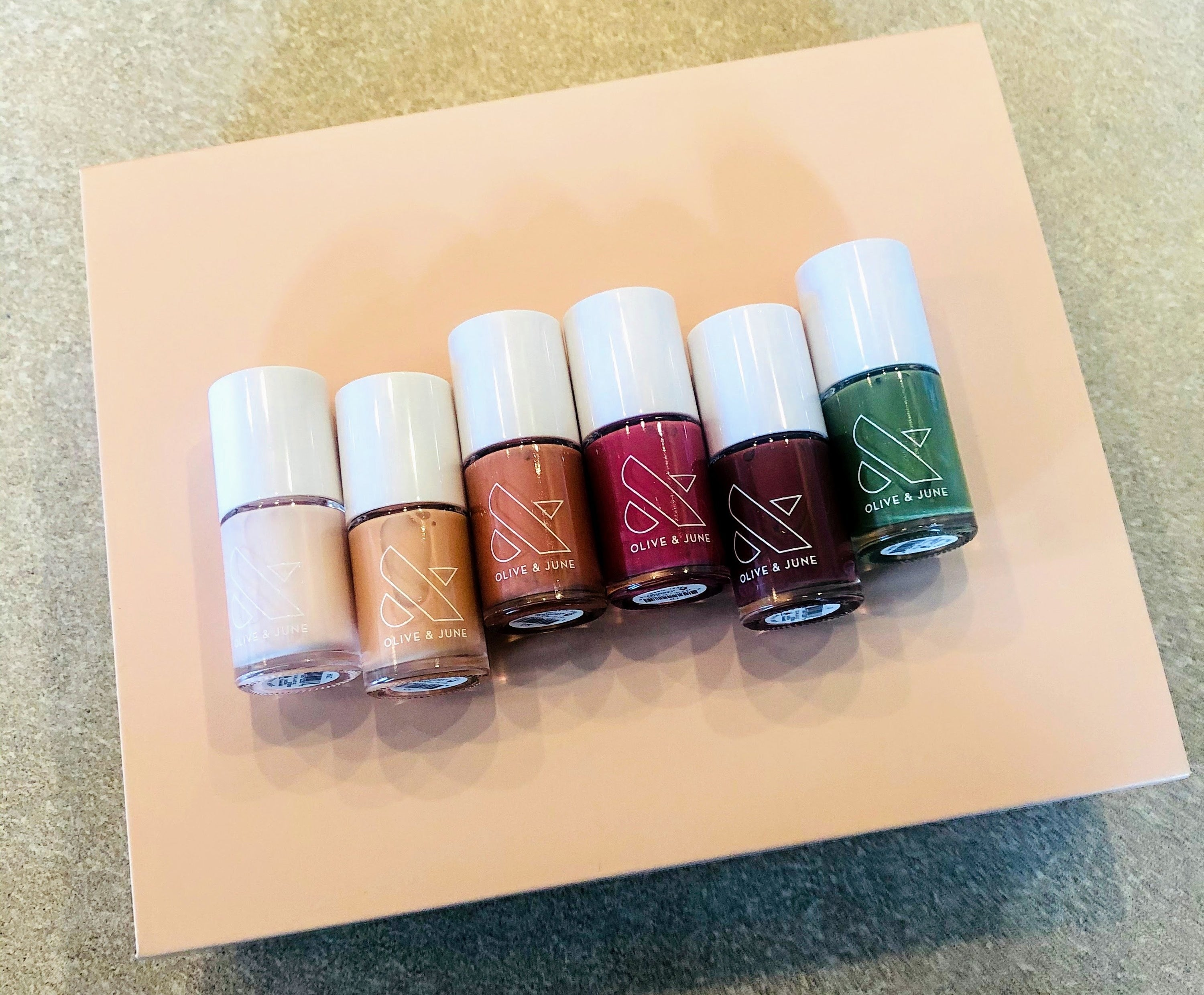 A cream box with six nail polish bottle on top in cream, yellow, orange, red, brown, and green.