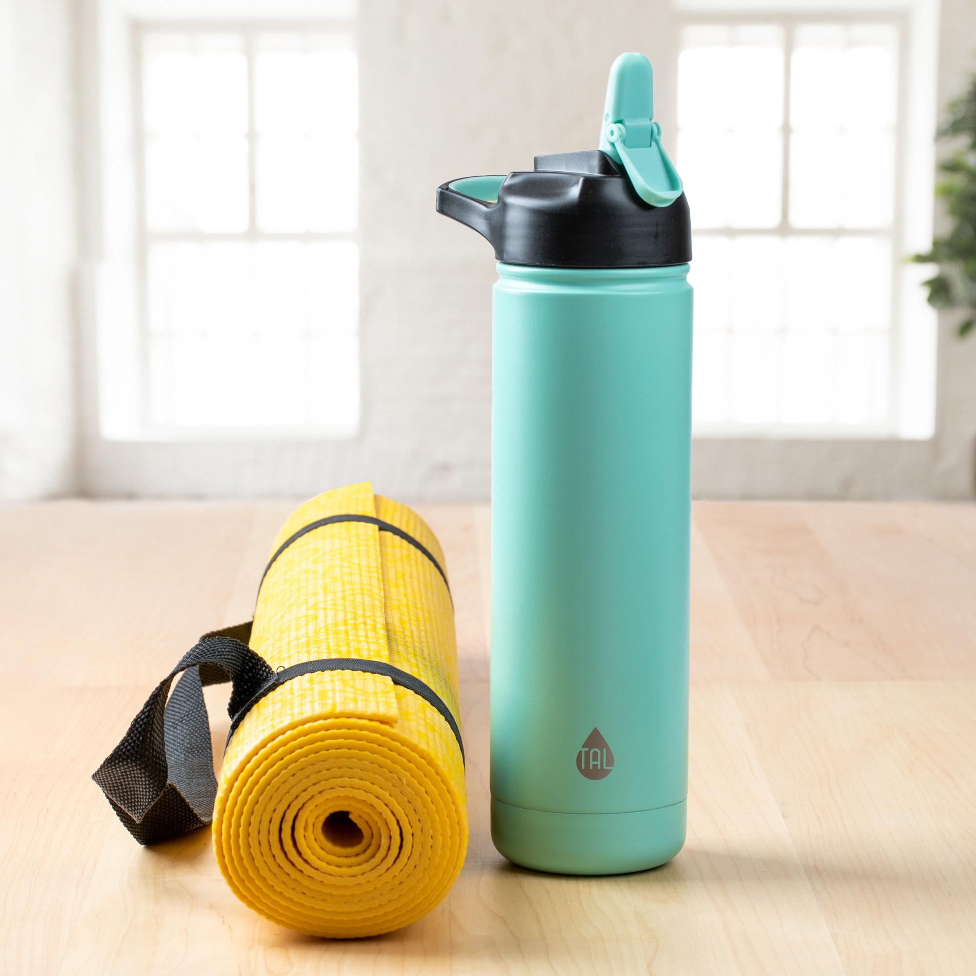 mint water bottle next to a yoga mat