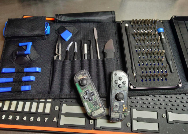 Reviewer uses black electronic repair kit with blue and black tools to fix a gaming controller