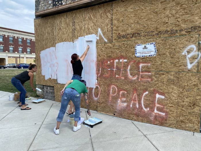 "People paint white over a wall that says ""No justice, no peace"""