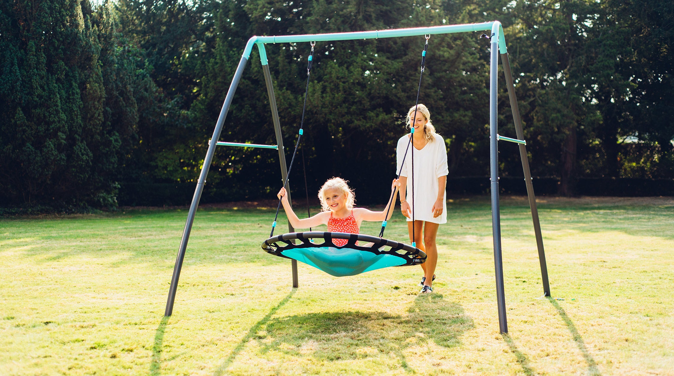 a mother pushing a girl in a metal nest swing