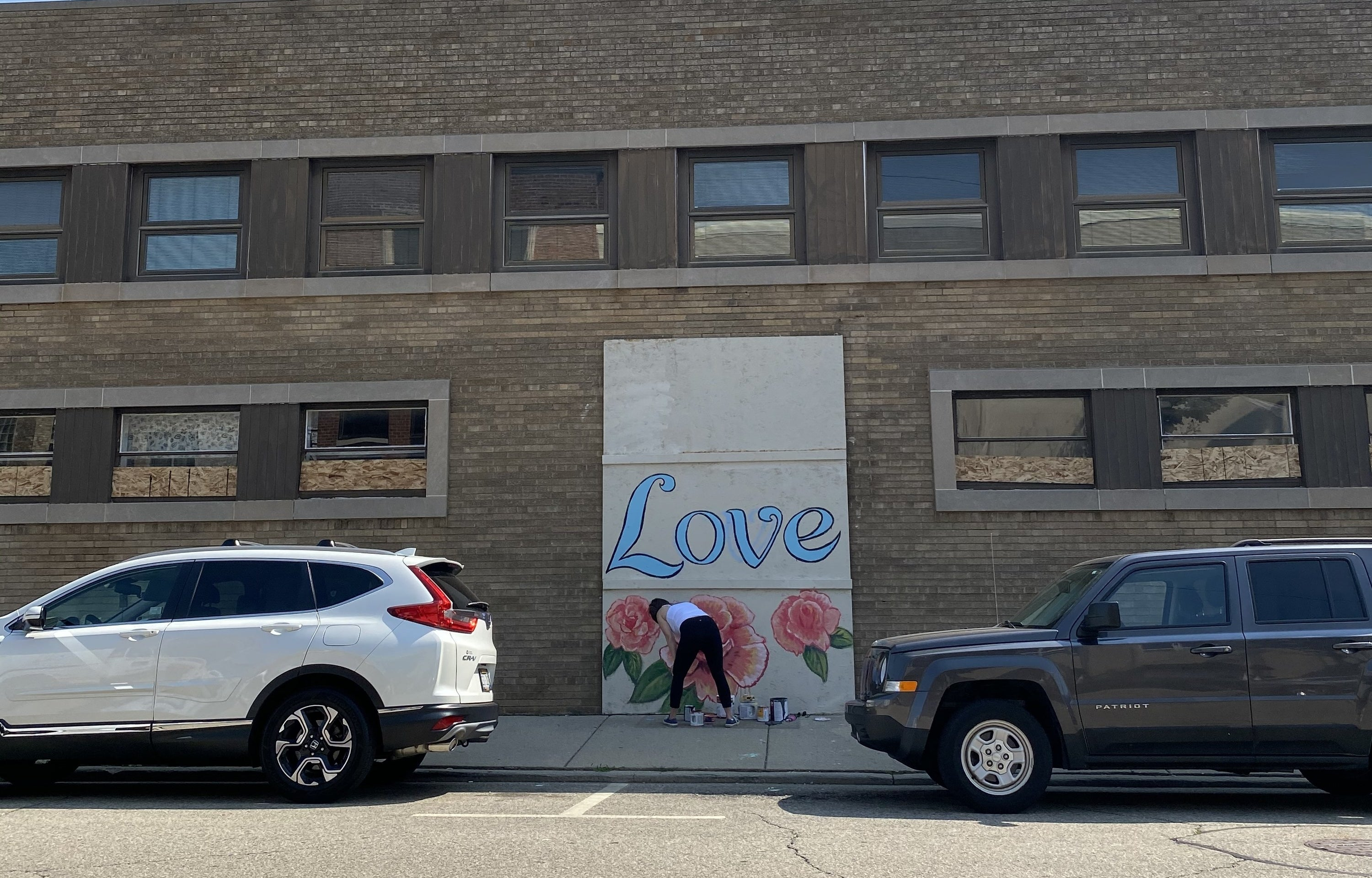 "A mural says ""Love"" with flowers below"
