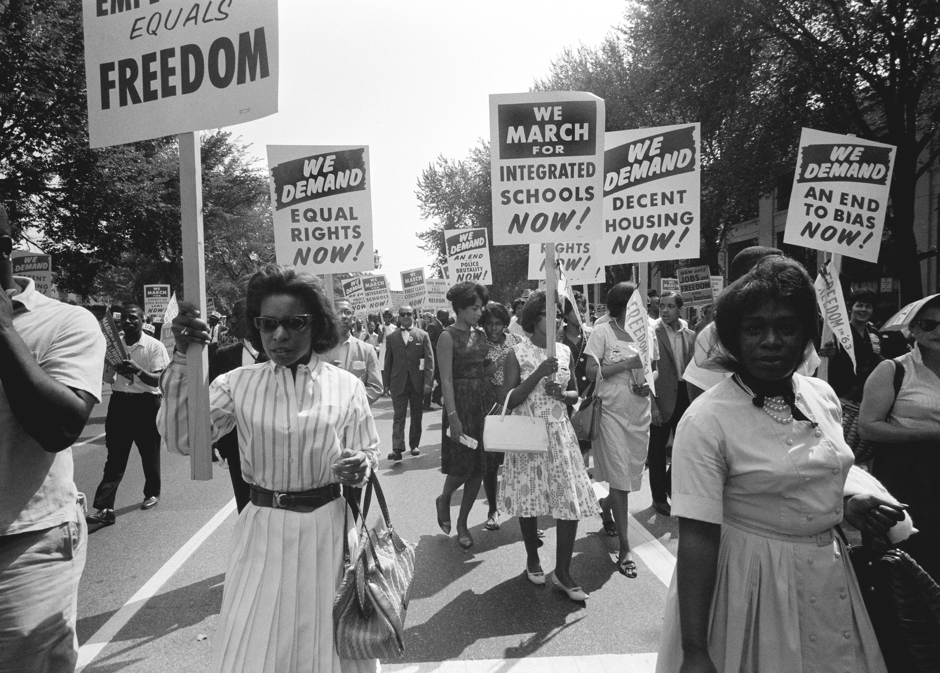 """Black women marching in the March on Washington with signs that say, """"We march for integrated schools nows,"""" """"We demand equal rights now,"""" """"We demand decent housing now,"""" and """"We demand an end to bias now."""""""