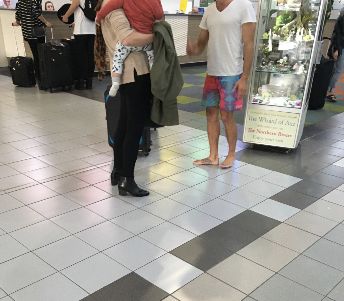 A barefoot man talking to some people