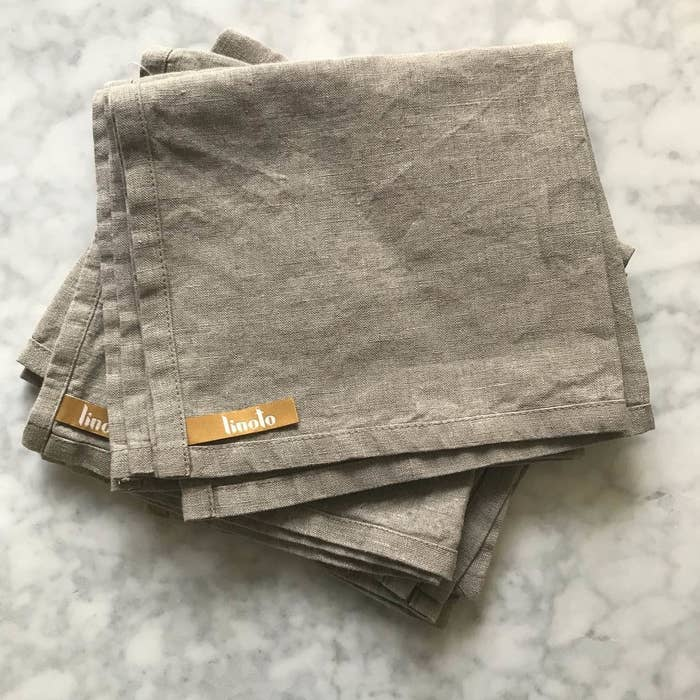 several folded tan linen towels with linoto labels