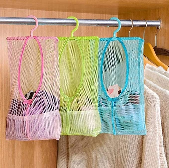 Clothes hanging in the mesh bags in the closet.