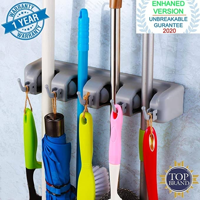 Adhesive wall mop holder with hooks.