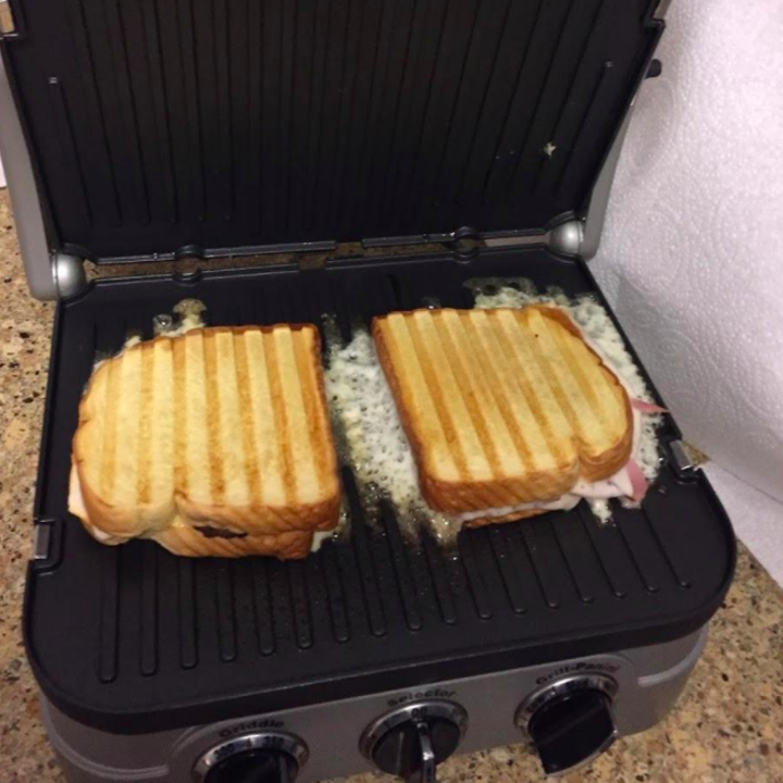 A reviewer making two paninis on the griddler