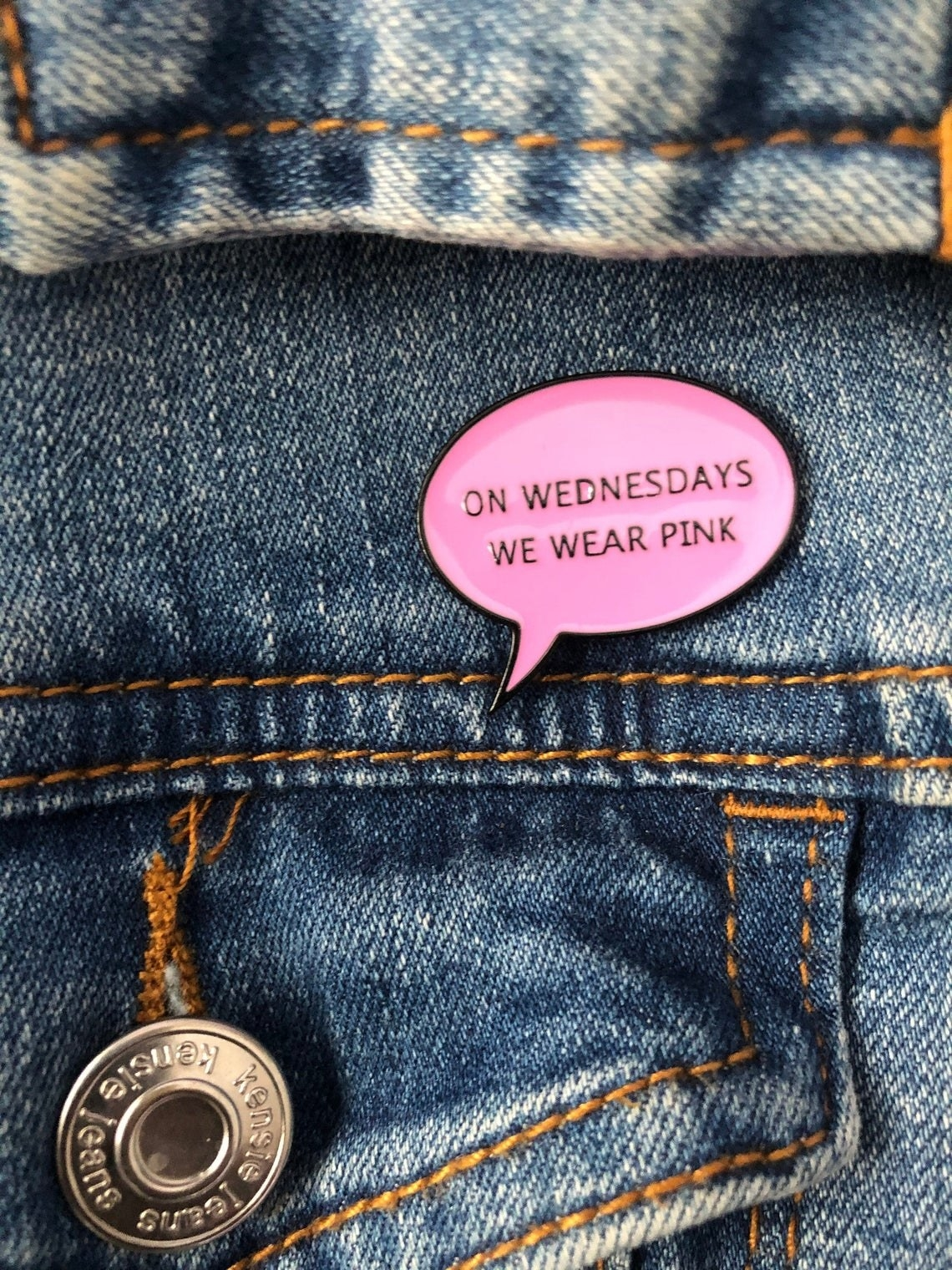 A small pin on a jean jacket that says on Wednesdays we wear pink