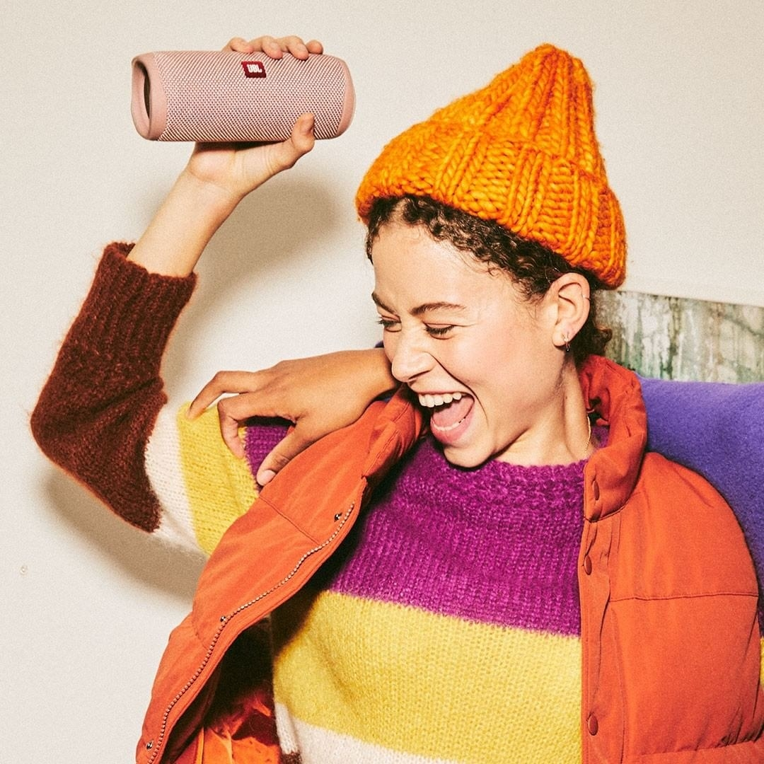 Model carries light pink JBL Flip 5 Waterproof Portable Bluetooth Speaker in their hand
