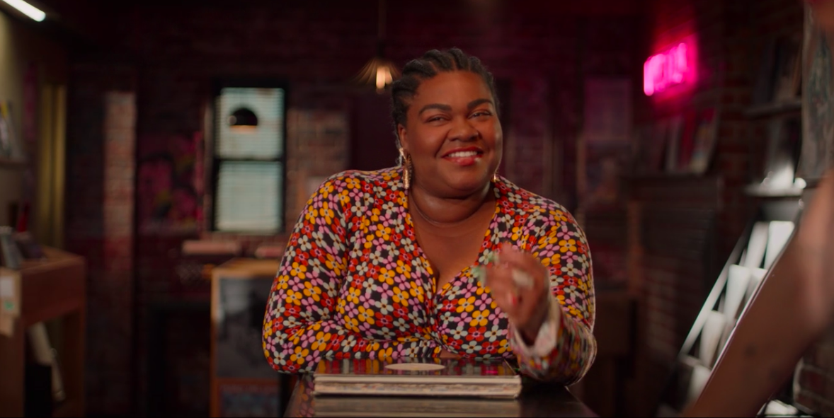 "A ""High Fidelity"" still of Da'Vine Joy Randolph wearing a pattern dress while smiling"