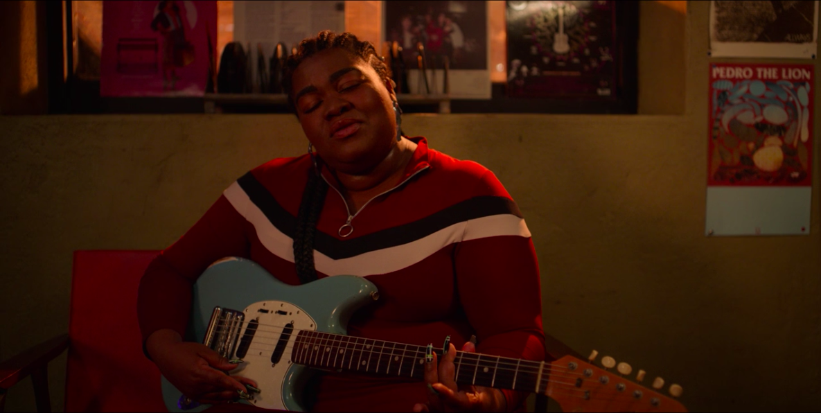 "A ""High Fidelity"" still of Da'Vine Joy Randolph singing while strumming her guitar"