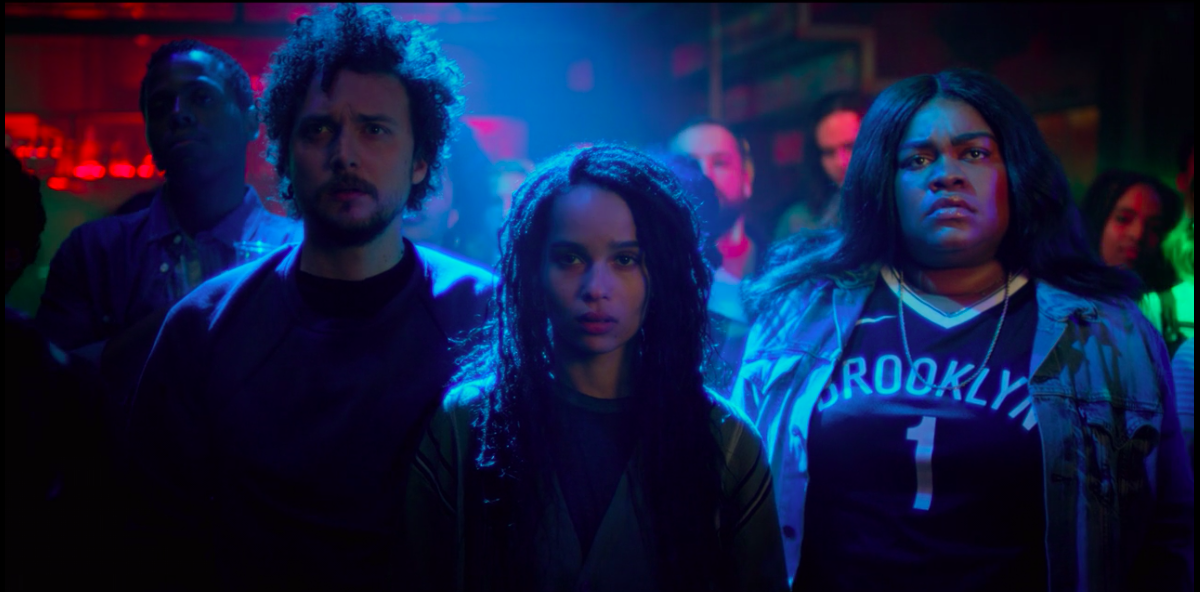 "A ""High Fidelity"" still of David H. Holmes, Zöe Kravitz, and Da'Vine Joy Randolph standing in the crowd of a concert"