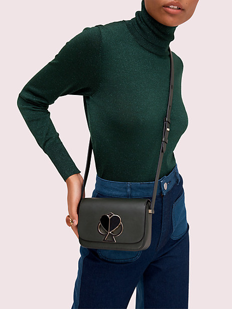 Model wearing a black crossbody flap bag with a metallic spade and heart closure