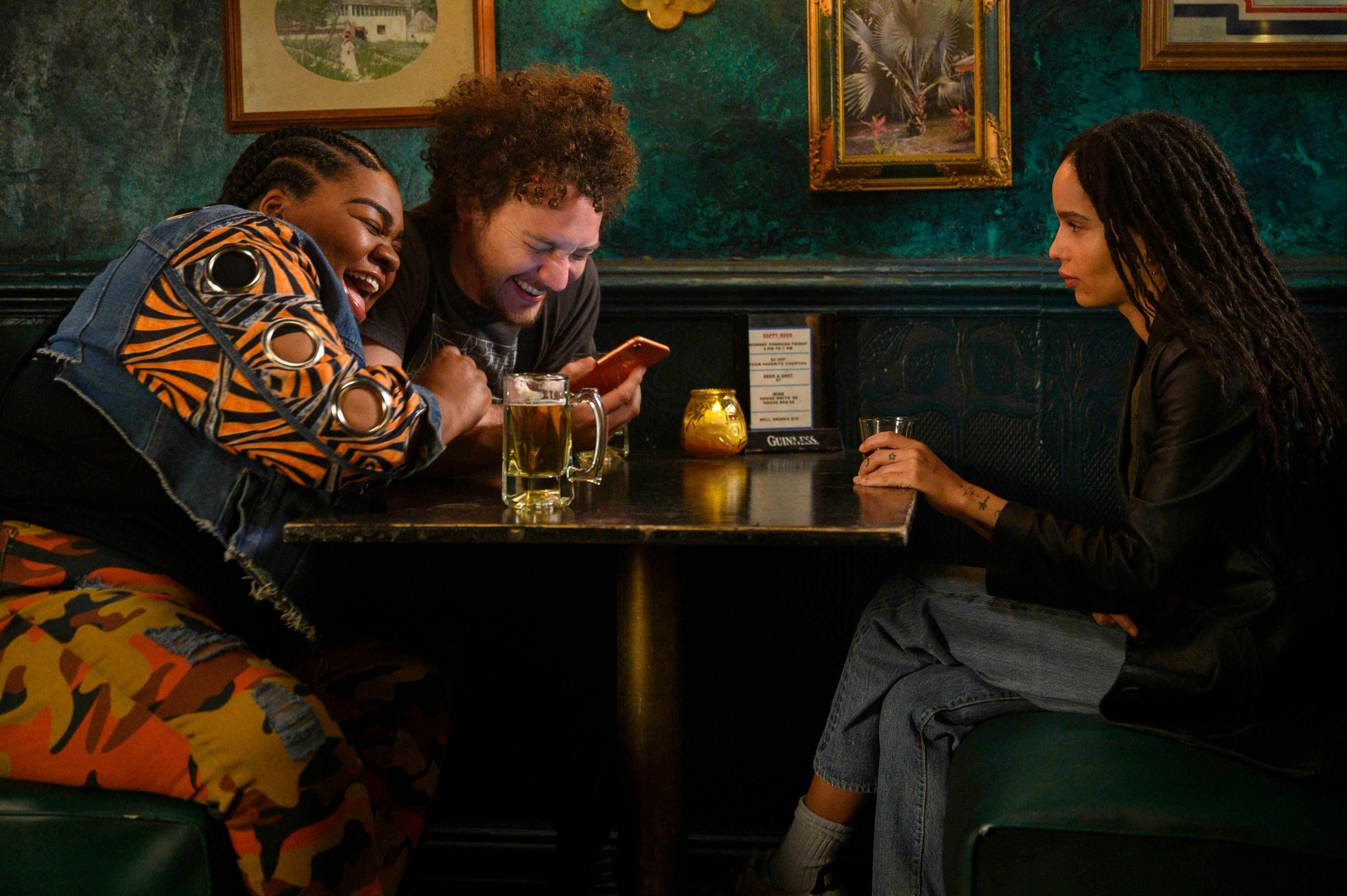 "A ""High Fidelity"" still of Da'Vine Joy Randolph and David H. Holmes laughing in a bar booth, while Zöe Kravitz stares at them"