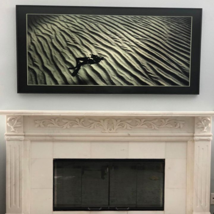 A different reviewer showing the same style TV with a black frame on the wall
