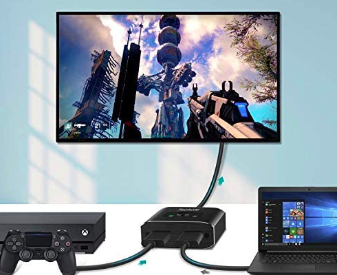 Black HDMI splitter connecting an Xbox, laptop, and smartTV in a living space