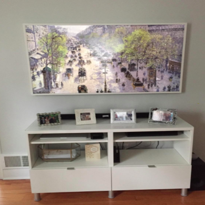 Reviewer showing the rectangle TV with a picture of a Victorian street on the wall