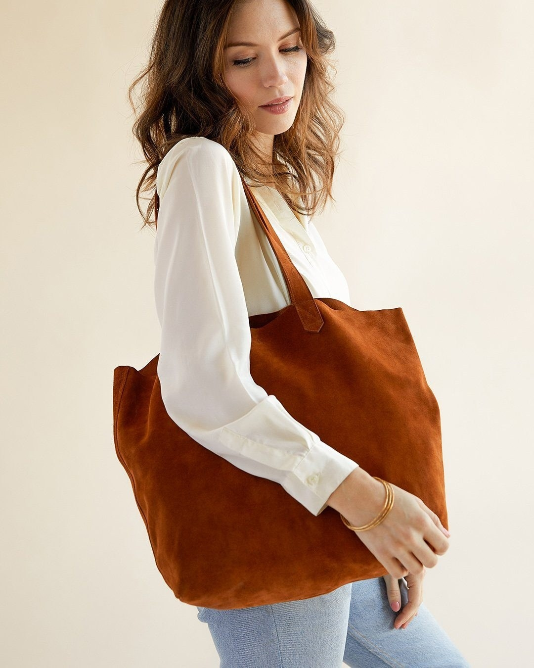 Model holding a brown suede oversized tote bag
