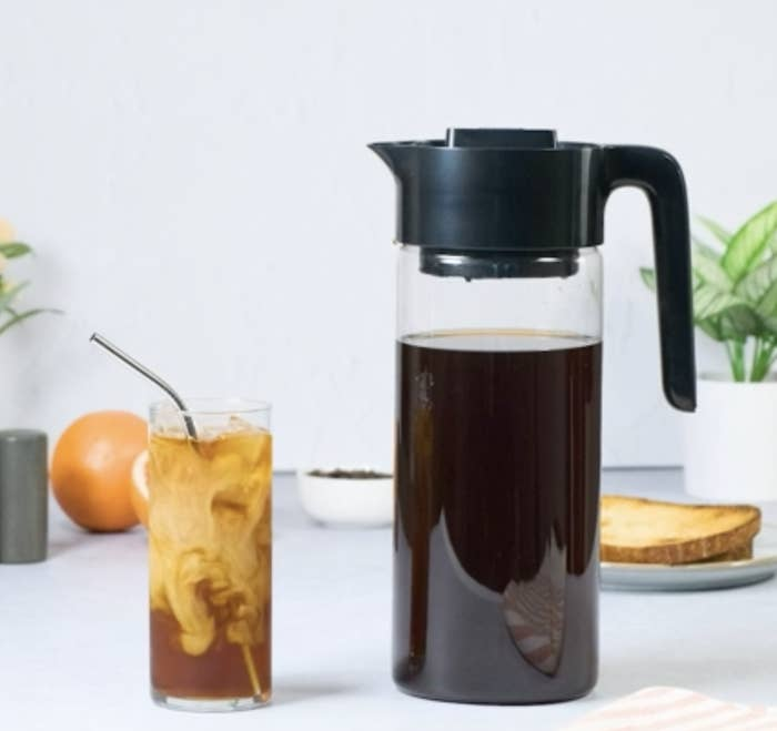 cold brew pitcher with handle and spout next to glass of iced coffee with milk