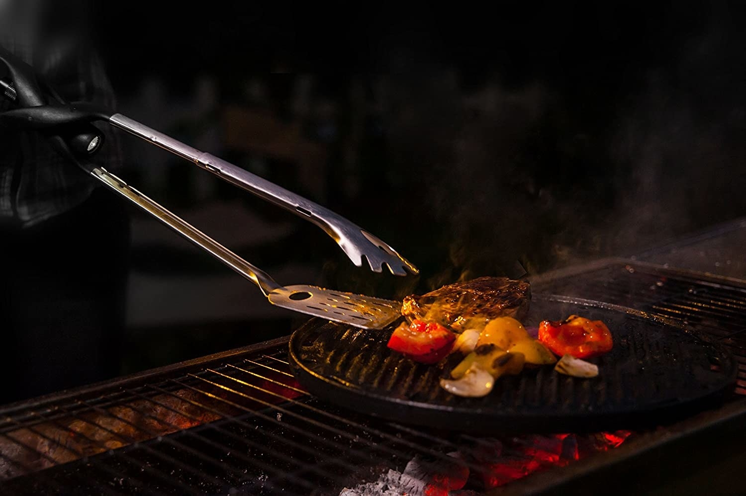 A model using the tool as tongs, as head of the tong is a spatula and the other a traditional tong, with a flashlight shining light from base between the tongs onto the food on the grill