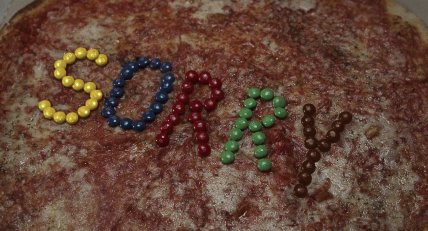 """A pizza with the word """"Sorry"""" written in M&Ms"""