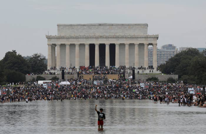 A young boy stands in the Reflecting Pool with his fist raised facing a big crowd leading up to the Lincoln Memorial