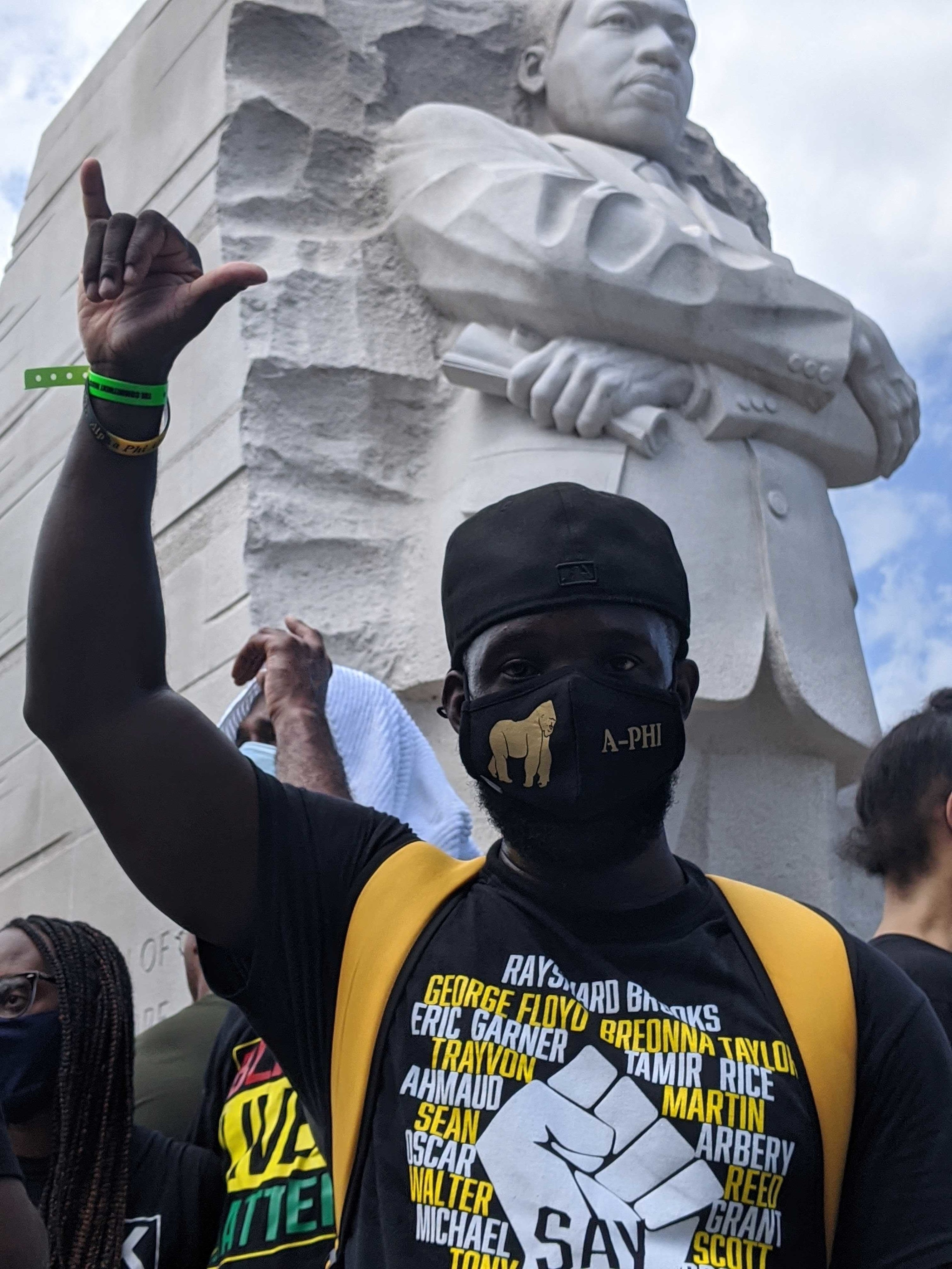 A man stands giving a hang loose sign with his hand in front of the Martin Luther King Jr memorial