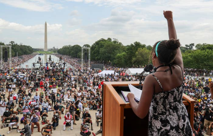A young woman stands at a podium with her fist raised in the air in front of a large crowd leading down the Reflecting Pool to the Washington Monument