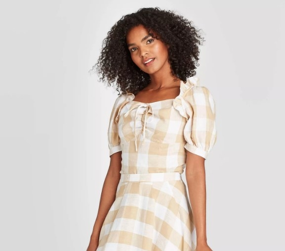 Model wearing the beige plaid top with puff sleeves