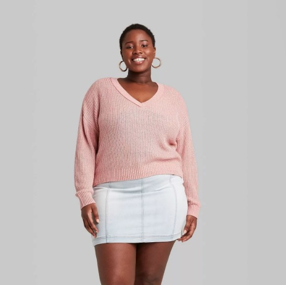 Model wearing the pink v-neck pullover sweater