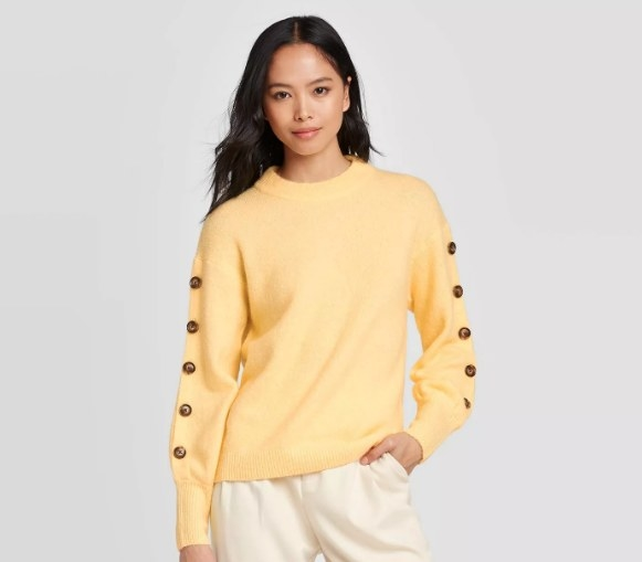 Model wearing the yellow sweater with buttons on the sleeves